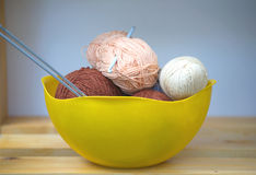 Color skeins of wool yarn, knitting needles and crochet hook in a big yellow bowl Royalty Free Stock Photo