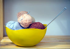 Color skeins of wool yarn, knitting needles and crochet hook in a big yellow bowl Stock Photos