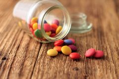 Color smarties around glass dose on wooden board Stock Photography