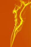 Color smoke. Yellow smoke texture at orange background Stock Image