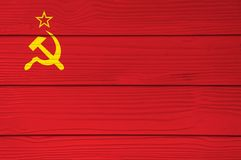 The color of Soviet Union flag painted on Fiber cement sheet wall background. a plain red flag with a golden hammer and sickle and. A gold-bordered red star in stock photography