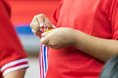 Color sports competition, The child received a gold medal from the sport and was repairing it. royalty free stock photography