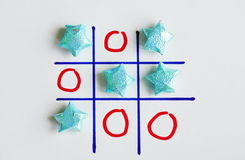 Color star paper in tic-tac-toe board game on white paper Stock Image
