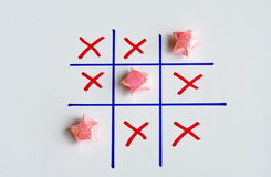 Color star paper in tic-tac-toe board game on white paper Stock Photography
