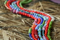 Color stones jewelry necklaces, straw background Royalty Free Stock Photos