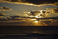 Color sunrise over the ocean. With sun star and 'God' rays Royalty Free Stock Photo
