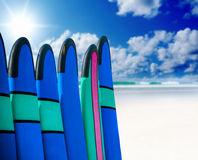 Color surf boards in a stack by ocean Stock Photos