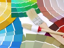 Color swatches. Two paint brushes on arrays of paint color swatches Royalty Free Stock Photography