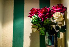 Color synthetic flowers on shelf corner royalty free stock photography