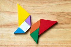 Color tangram puzzle in flying butterfly shape. On wood background royalty free stock photos