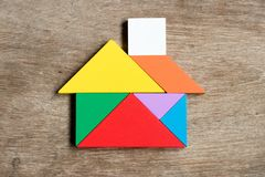 Color tangram puzzle in house shape. On wood background Royalty Free Stock Images