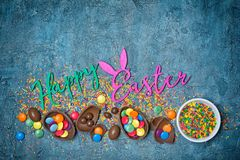 Color text of happy easter with chocolate traditional eggs and sugar sprinkles or confetti