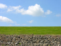 Color and texture. A view of the sky with green grass and rocks in the foreground Stock Photos