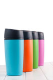 Color thermos mugs on the white table Royalty Free Stock Image