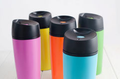 Color thermos mugs on the white wooden table Stock Photos