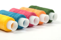 Color thread reels over white background. Selective focus stock photography