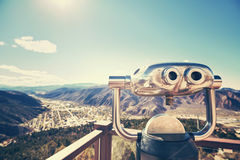 Color toned photo of binoculars looking out over a valley. Royalty Free Stock Images