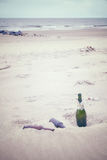 Color toned picture of empty liquor bottles left on a beach. Royalty Free Stock Photos