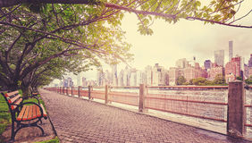 Color toned picture of walking path in Roosevelt Island, NYC. Color toned picture of a promenade in Roosevelt Island with view of Manhattan, focus on buildings royalty free stock photo