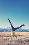 Color toned picture of young woman upside down on a meadow. Stock Image