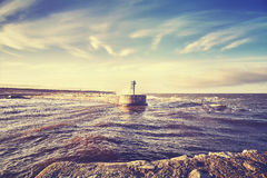 Color toned s sunset over port entrance beacon. Royalty Free Stock Photo