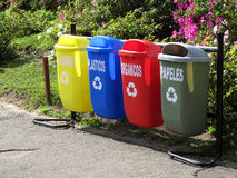 Color trash cans for garbage separation. Bright color trash cans for garbage separation in the city blossoming park Royalty Free Stock Photography
