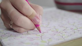 Color video of a woman hand holding a pencil drawing and coloring coloring book. Activity for relaxing and concentrate