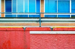 Color wall. Colorful textured wall, window and banister. all in vivid red, blue yellow and brown colors. This is an outside view of a public spanish hospital Stock Image