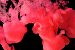 Color in a water. Red color movement in a water on black background stock images