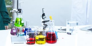 Color water in test tube and beaker near microscope at laboratory. Copy space on white science lab royalty free stock image