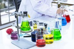 Color water in test tube and beaker near microscope at laboratory. Copy space on white science lab stock image