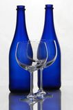 Color wine bottles and wine glasses. On a white background with reflections Royalty Free Stock Images