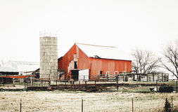 Color of Winter on the Farm. Heavily weathered old red barn with a grain silo directly in front of it, in a rural field surrounded by barbed wire fence during Royalty Free Stock Image