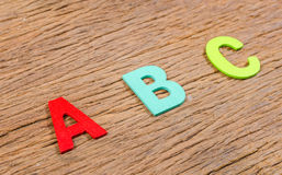Color wooden alphabet letter. On wooden board background Stock Photos