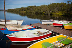 Color Wooden Boats with Paddles in a Lake Royalty Free Stock Images