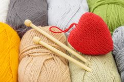 Handmade red heart and skeins of yarn for knitting. The concept of comfort and love stock photos