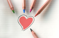 Color your heart - red. Colored pencils on white background with red heart Royalty Free Stock Photo
