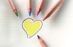 Color your heart - yellow. Colored pencils on white background with yellow heart Royalty Free Stock Photo