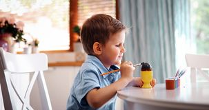 A coloração do menino da criança eggs para o feriado da Páscoa na cozinha doméstica imagem de stock
