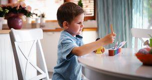 A coloração do menino da criança eggs para o feriado da Páscoa na cozinha doméstica foto de stock royalty free