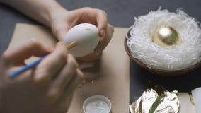 A coloração eggs para a Páscoa com mãos e uma escova com pinturas da aquarela Ninho e grinalda filme