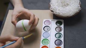A coloração eggs para a Páscoa com mãos e uma escova com pinturas da aquarela Ninho e grinalda video estoque