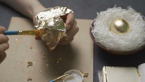 A coloração eggs para a Páscoa com mãos e uma escova com pinturas da aquarela vídeos de arquivo
