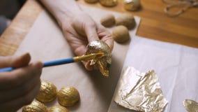 A coloração eggs para a Páscoa com mãos e uma escova com pinturas da aquarela video estoque