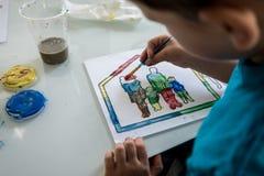 Coloração nova do menino em um esboço do esboço com pintura Imagem de Stock