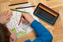 Coloração nova do menino no assoalho Fotos de Stock Royalty Free