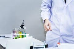 Colora a água no tubo de ensaio, nos microscópios e na taça Copie o espaço foto de stock