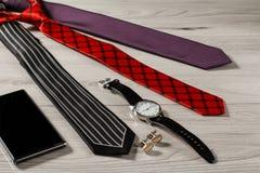 Colora as gravatas de seda, relógio, botão de punho, telefone da venda em uma madeira cinzenta Fotos de Stock Royalty Free