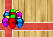 Colora balões do partido e a fita vermelha no fundo de madeira Fotos de Stock Royalty Free