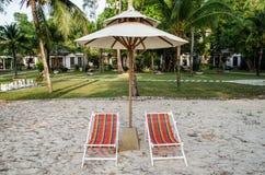 Cadeiras de praia da cor e guarda-chuva branco Fotografia de Stock